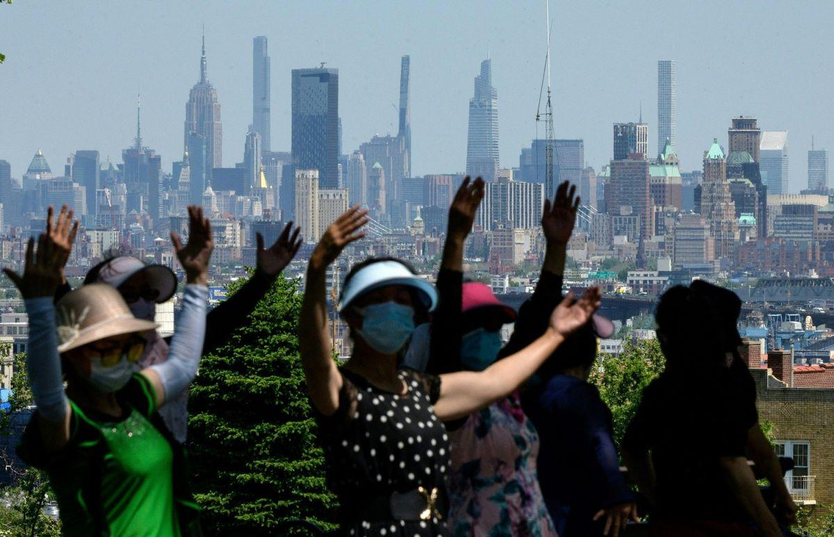 Un grupo de personas realizan actividades al aire libre con el paisaj de Manhattan al fondo.