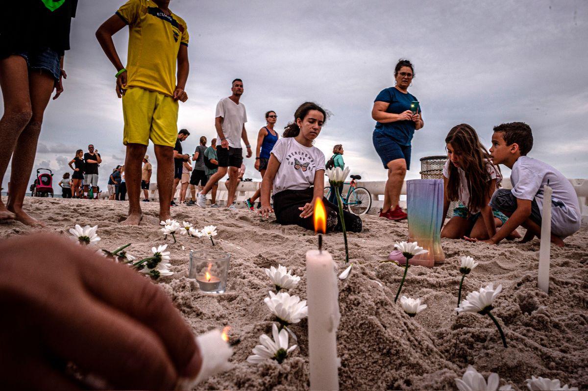Unos niños encienden velas en una vigilia en memoria de los desaparecidos en el derrumbe del edificio en Surfside,