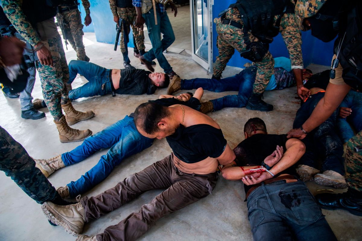 Policías custodian a un grupo de sospechosos de haber participado en el asesinato del presidente haitiano, Jovenel Moise, en Puerto Príncipe.