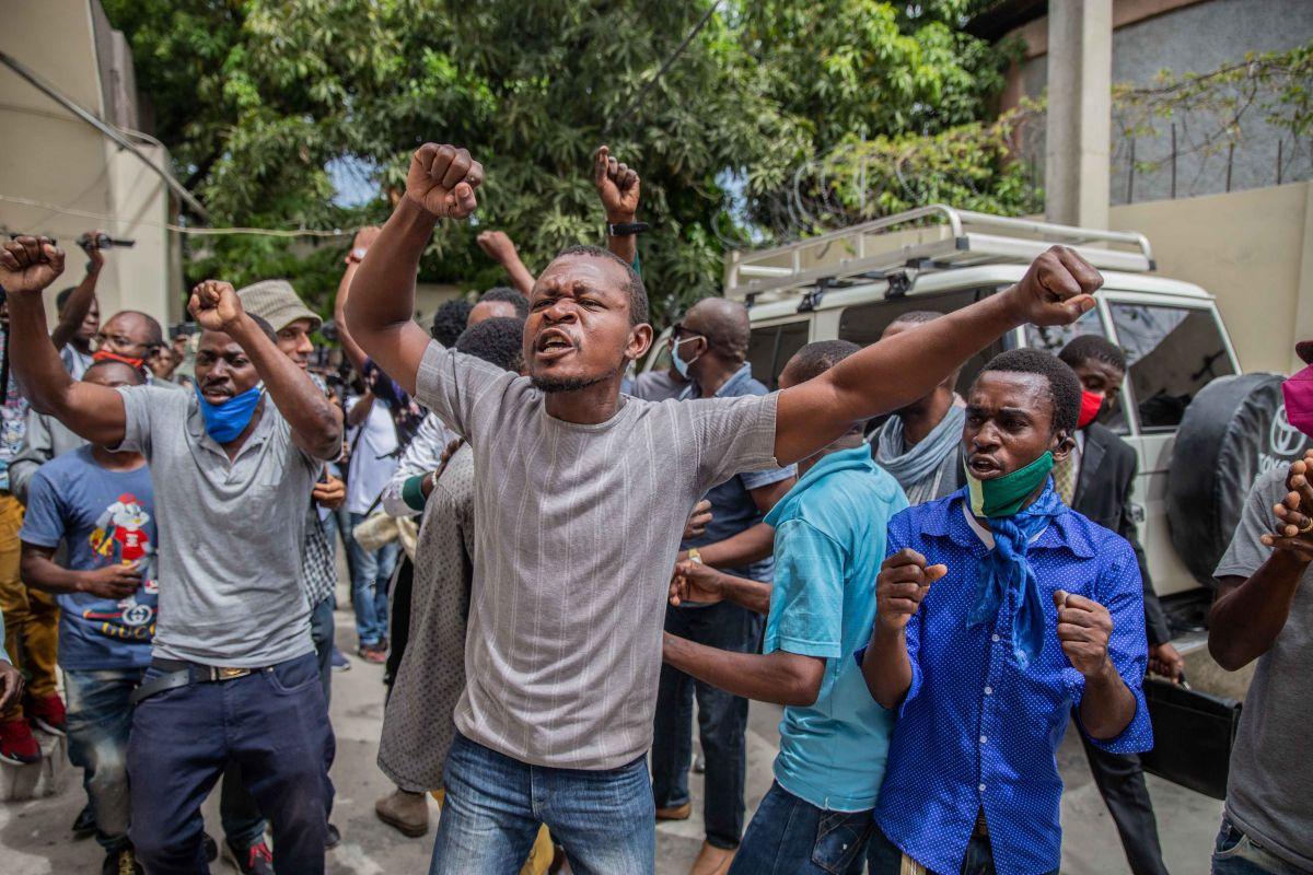 Seguidores del exsenador haitiano Youri Latortue protestan en el exterior de la corte en Puerto Príncipe donde el político fue entrevistado en relación con el asesinato del presidente Jovenel Moïse.