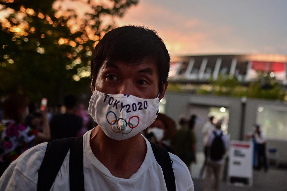 Un hombre lleva una mascarilla con los colores olímpicos.