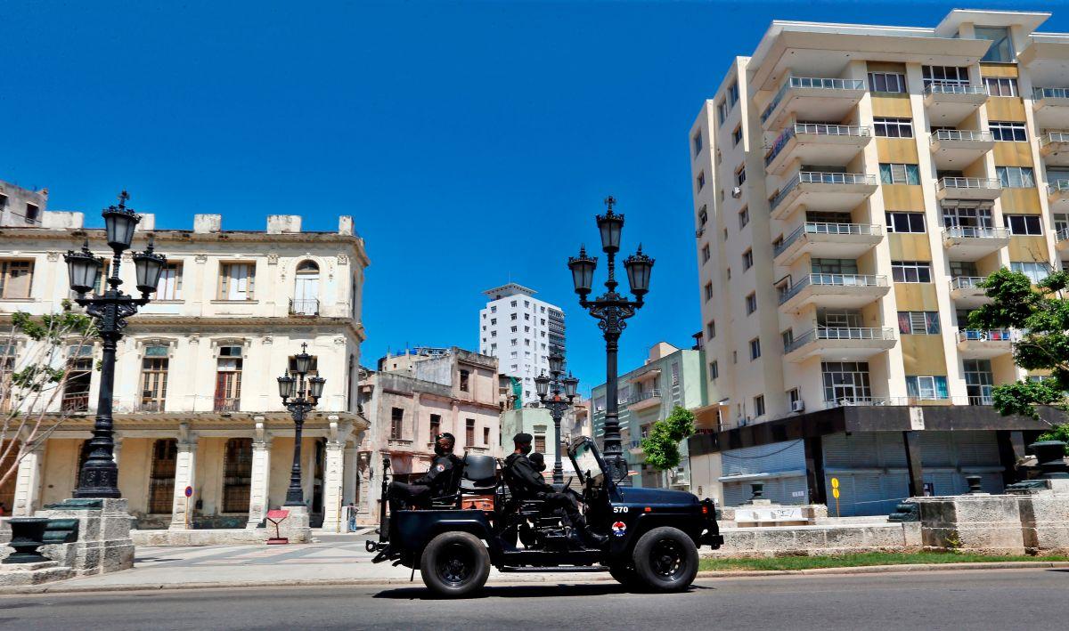 Varios policías de una brigada especial se transportan en vehículo por una calle en La Habana, Cuba.