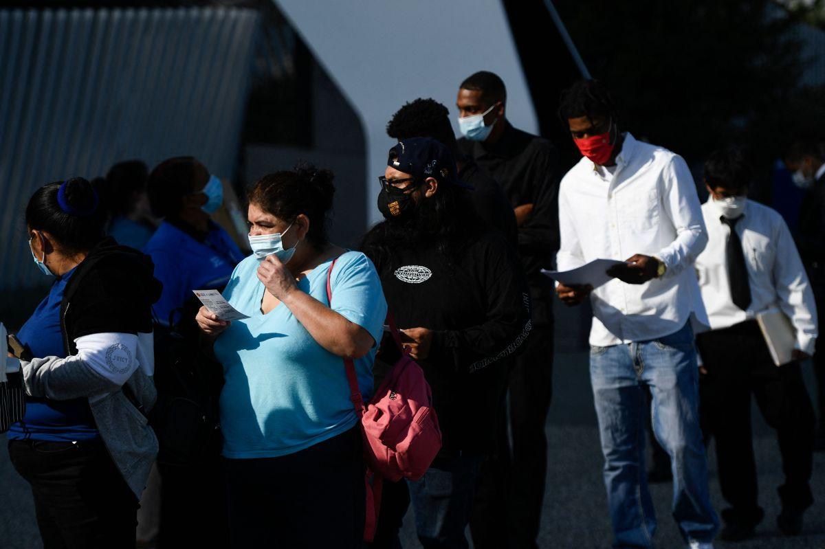 Personas esperan en la fila para asistir a una feria de empleo en EE.UU.